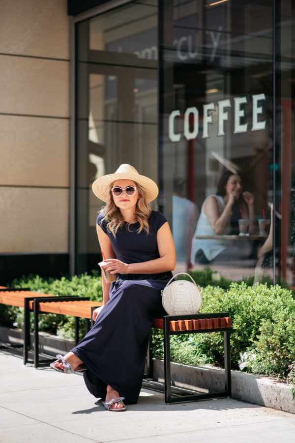 Personal Stylist Jessica Sturdy styling a straw hat and navy blue maxi dress with a round handbag and bow slides for a quick coffee run in Chicago's Gold Coast at La Colombe.