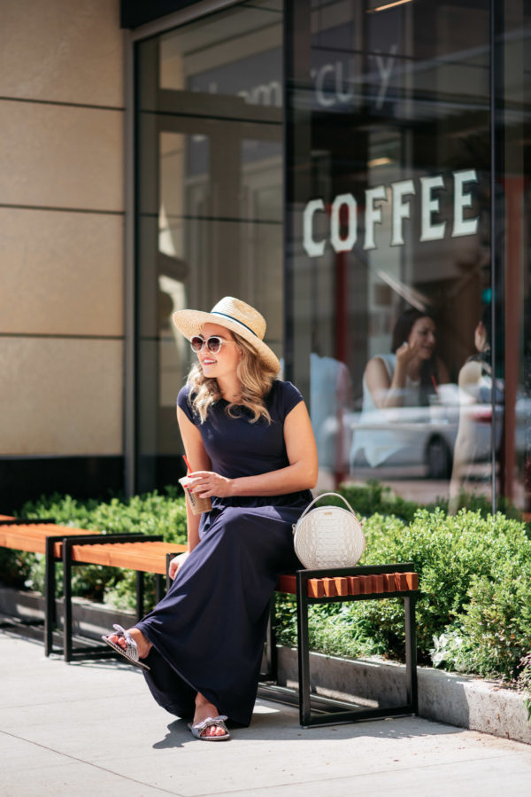 Chicago personal shopper Jessica Sturdy wearing a navy blue maxi dress with a striped straw hat, white circle bag by Brahmin, blue and white printed bow slides from J.Crew.