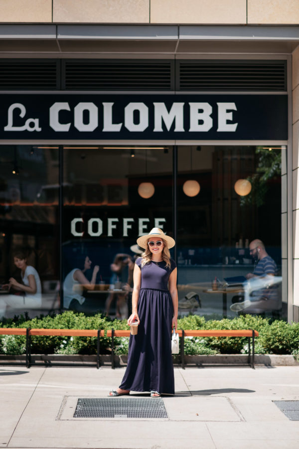 Chicago lifestyle blogger Jessica Sturdy at La Colombe Coffee in Chicago's Gold Coast neighborhood wearing a blue maxi dress, straw hat, and circle handbag.