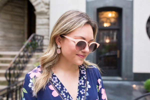 Bows & Sequins wearing a floral dress with peach colored sunglasses.