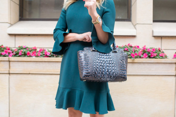 Chicago fashion blogger styling a green dress with a beautiful navy handbag.