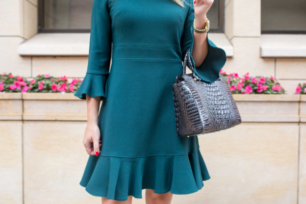 Chicago fashion and style blogger wearing a ruffled work dress with a navy blue work tote.