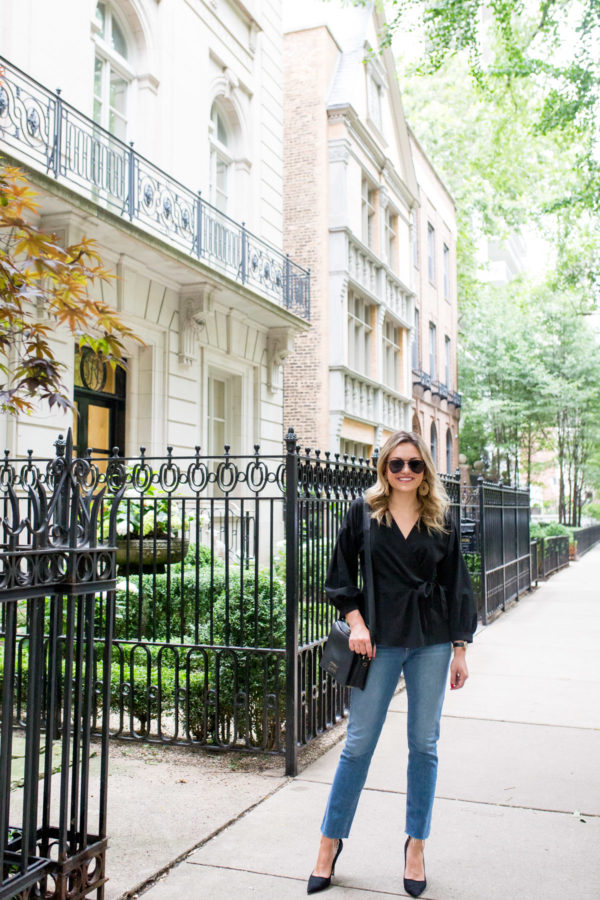 Chicago travel blogger Jessica Sturdy wearing a black wrap blouse with jeans for Casual Friday at the office.