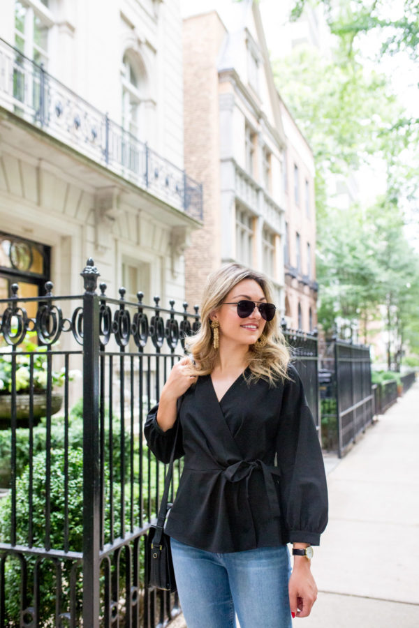 Chicago beauty blogger wearing a black wrap blouse with matte black sunglasses and gold statement earrings.