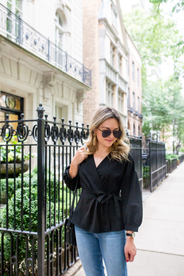 Chicago blogger Bows & Sequins wearing a black wrap top for the office with light jeans.
