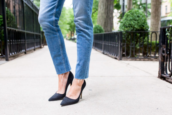 Bows & Sequins styling raw hem jeans with black Kate Spade pumps.