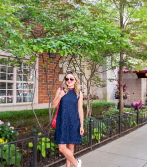 Chicago fashion blogger Jessica Sturdy wearing a navy blue lace dress with white Stan Smith sneakers in the Gold Coast.