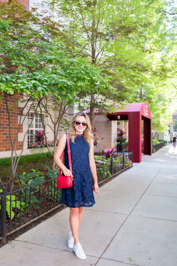 Jessica Sturdy wearing a Halogen navy blue lace dress with a red crossbody bag, Gucci aviators, and white Stan Smith sneakers.