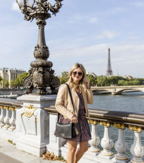 Jessica Sturdy (blogger behind Bows & Sequins) in Paris on a gorgeous, sunny September Day. She is on one of the prettiest, gilded bridges in Paris, with magnificent views of the Eiffel Tower. She's wearing a Sandro leather jacket, a flirty floral dress, and a Lancel Pia bag.