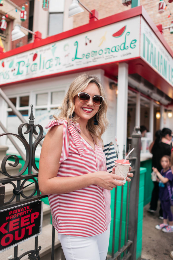 Top Chicago blogger Jessica Sturdy wearing a striped tank top with a bow-tie on the shoulder in front of Mario's Italian Lemonade in Chicago.