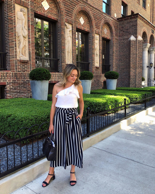 Jessica Sturdy at Restoration Hardware in Chicago wearing a ruffled one-shoulder crop top blouse with striped wide leg pants.