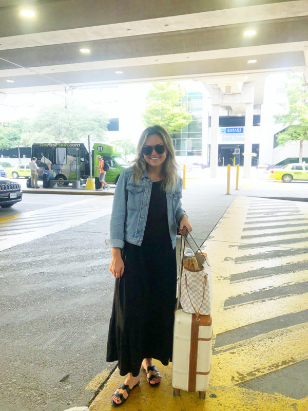 Travel blogger at Austin Texas airport wearing a black maxi dress, denim jacket, Louis Vuitton neverfull bag, and Bric's Bellagio suitcase.