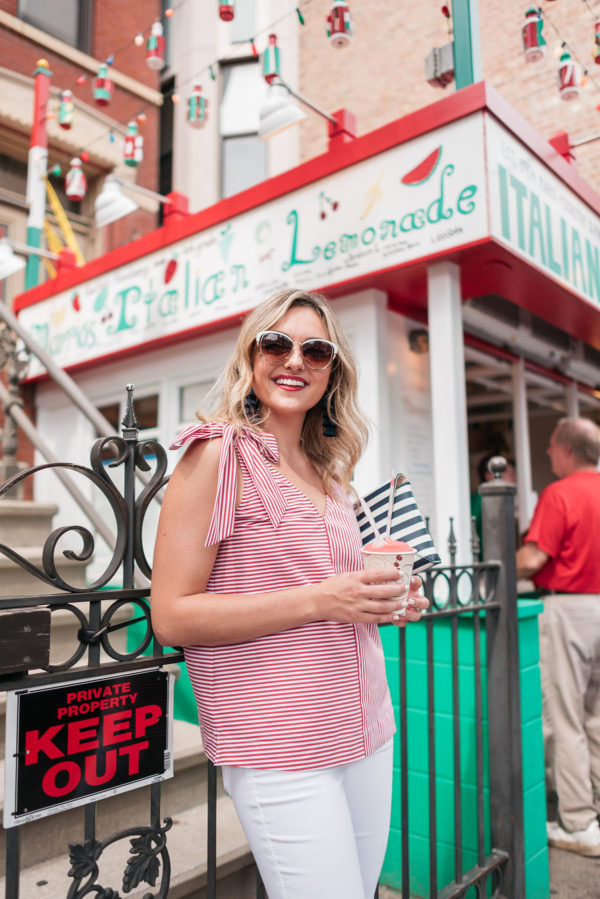 Chicago lifestyle blogger Jessica Sturdy wearing a red and white striped top from Vineyard Vines with a bow shoulder in Chicago's Little Italy neighborhood in front of Mario's Italian Lemonade.