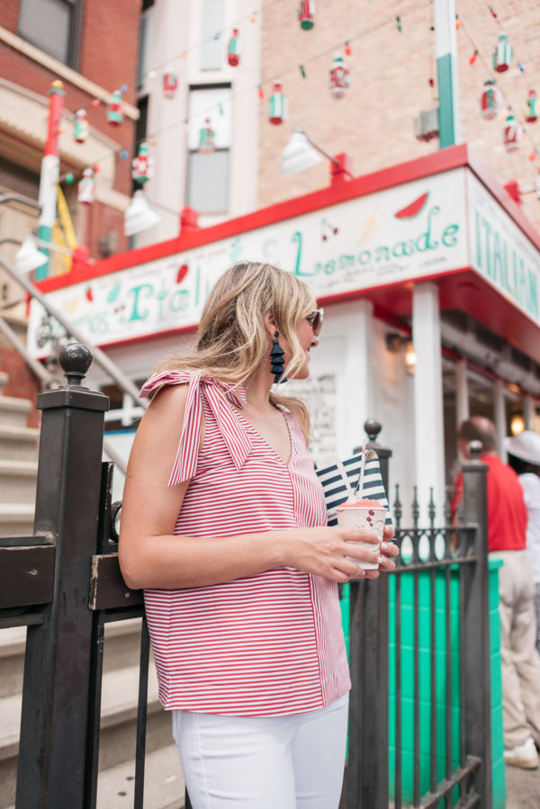 Chicago travel blogger Jessica Sturdy wearing a red and white striped top with a bow, BaubleBar tassel earrings, and a J.Crew navy and white striped clutch in front of a cute lemonade stand in Little Italy.