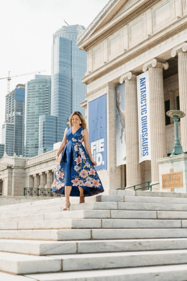 Chicago fashion blogger Jessica Sturdy wearing a blue floral dress in front of the Field Museum in Chicago for a wedding.