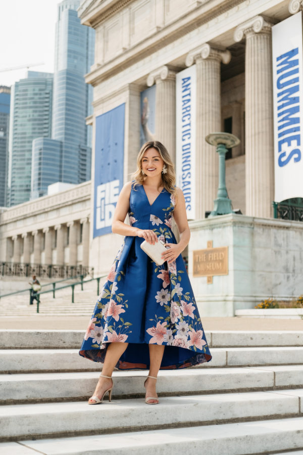 Chicago fashion blogger Jessica Sturdy wearing a floral fit and flare dress with nude heels and a small gold clutch for a black tie wedding guest attire.