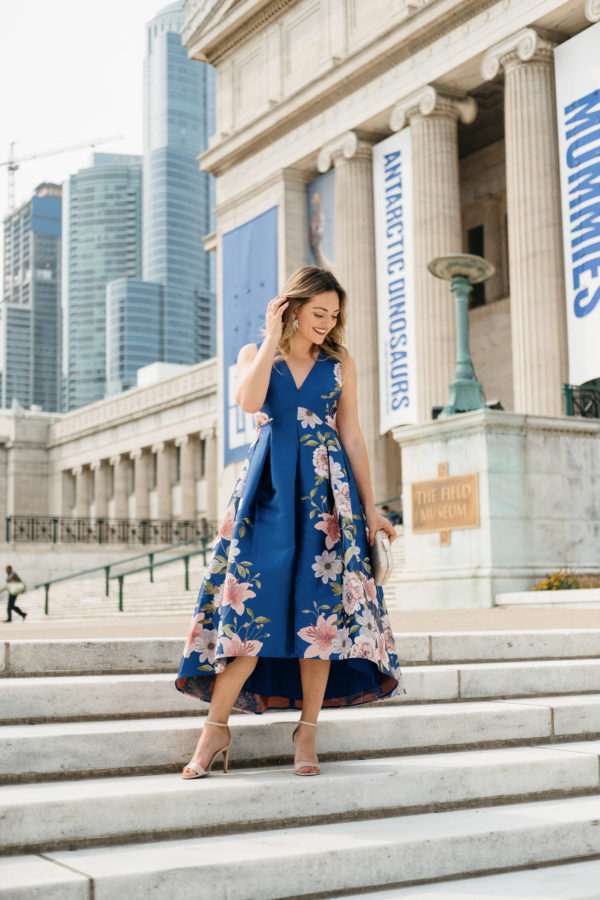 Chicago fashion and beauty blogger Jessica Sturdy wearing a blue floral fit and flare dress on the steps in front of the Field Museum in Chicago.