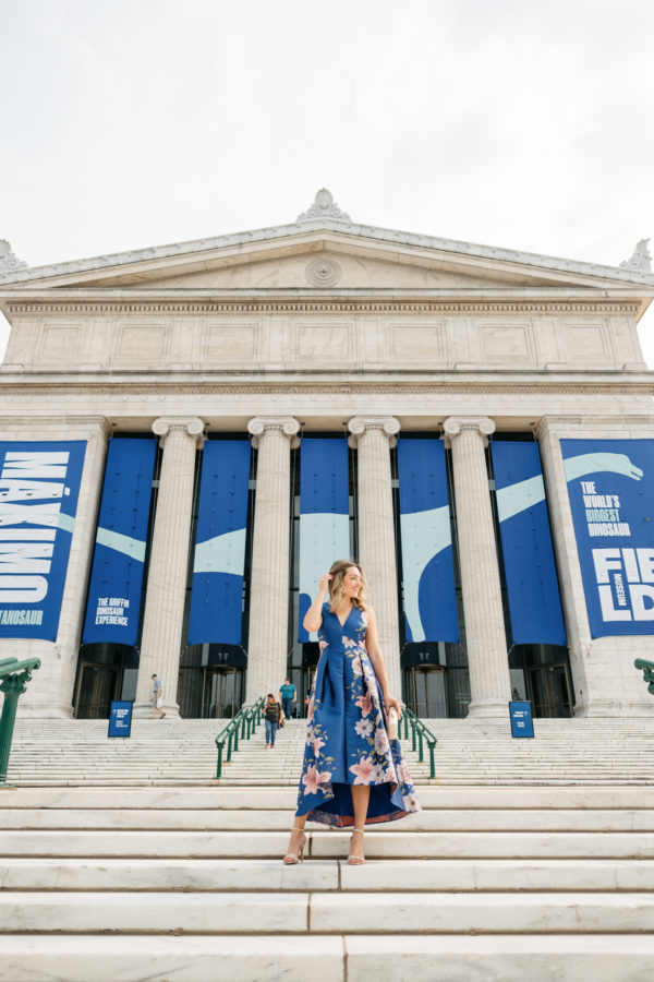 Chicago fashion blogger Bows & Sequins wearing a blue floral dress in front of the Field Museum for a fancy wedding.
