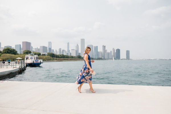 Bows & Sequins wearing a floral high-low hem dress in front of the Chicago skyline on Lake Michigan.