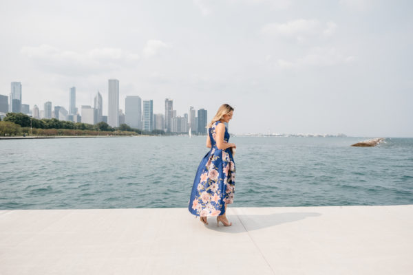 Chicago-based fashion Instagrammer Jessica Sturdy in front of Lake Michigan and the Chicago skyline wearing a formal blue and pink floral dress.
