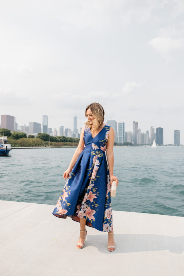 Fashion blogger Jessica Sturdy wearing a pretty blue and pink floral dress by Lake Michigan with the Chicago skyline in the background, one of the best places to take photos in Chicago.