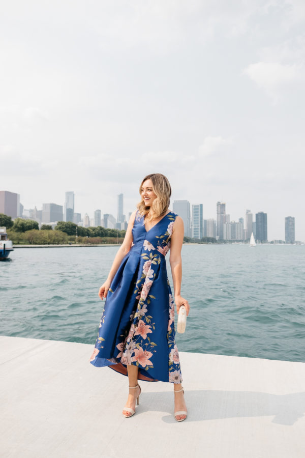 Chicago blogger Jessica Sturdy wearing a pink and blue floral dress by Lake Michigan with the skyline in the background.