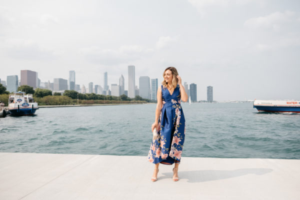 Fashion blogger Jessica Sturdy wearing a blue floral dress in front of the Chicago skyline along Lake Michigan by Museum Campus.