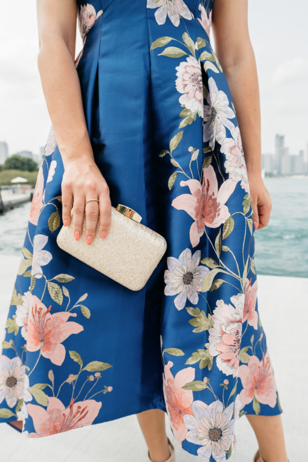Bows & Sequins wearing a floral fit and flare dress by Eliza J with a pretty gold clutch from Nordstrom.
