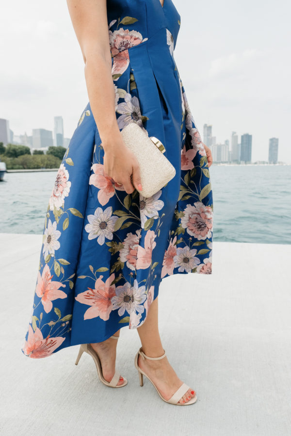 Bows & Sequins styling a floral blue and pink dress with nude ankle strap heels and a mini gold formal clutch from Nordstrom.