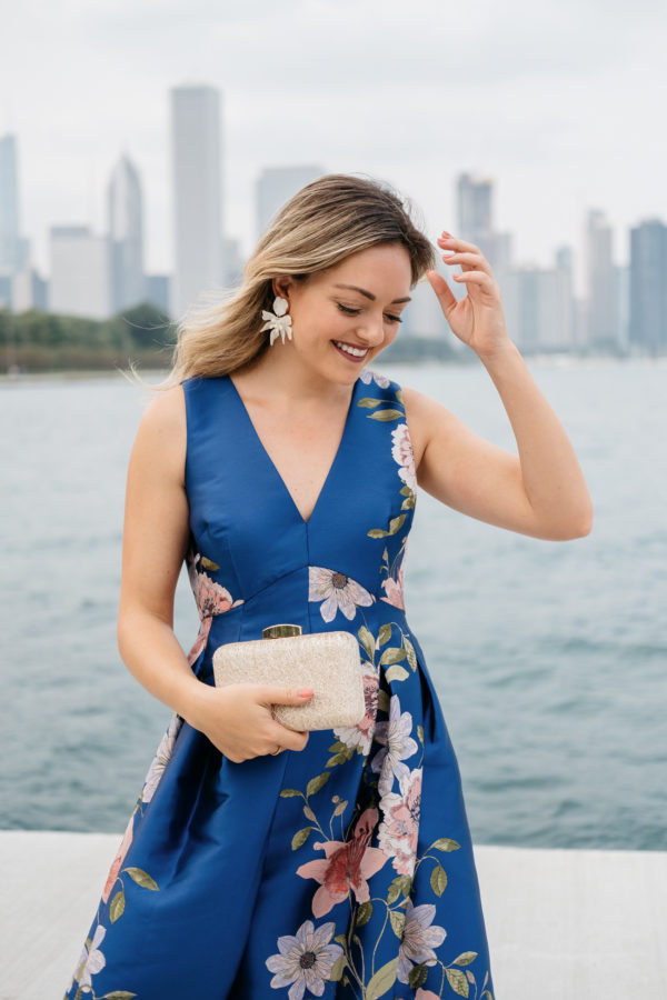 Chicago fashion blogger Bows & Sequins wearing a floral Eliza J dress with a gold clutch and white floral earrings from Lele Sadoughi.