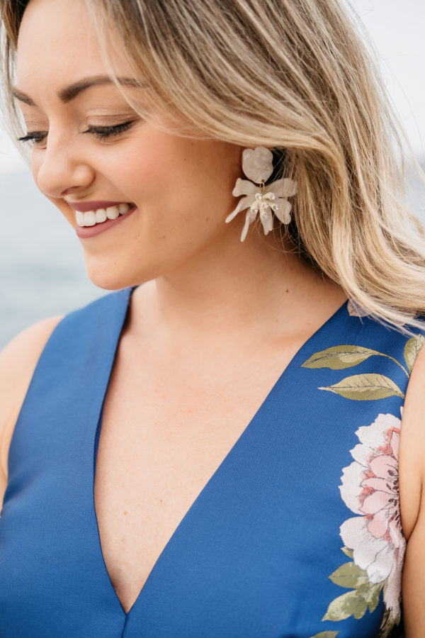 Chicago fashion and beauty blogger Jessica Sturdy styling white daffodil Lele Sadhoughi earrings with a blue satin floral dress by Eliza J from Nordstrom.