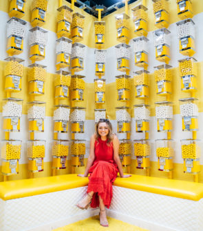 Fashion blogger Jessica Sturdy at Happy Place in Chicago sitting in front of the yellow and white gumball machines.
