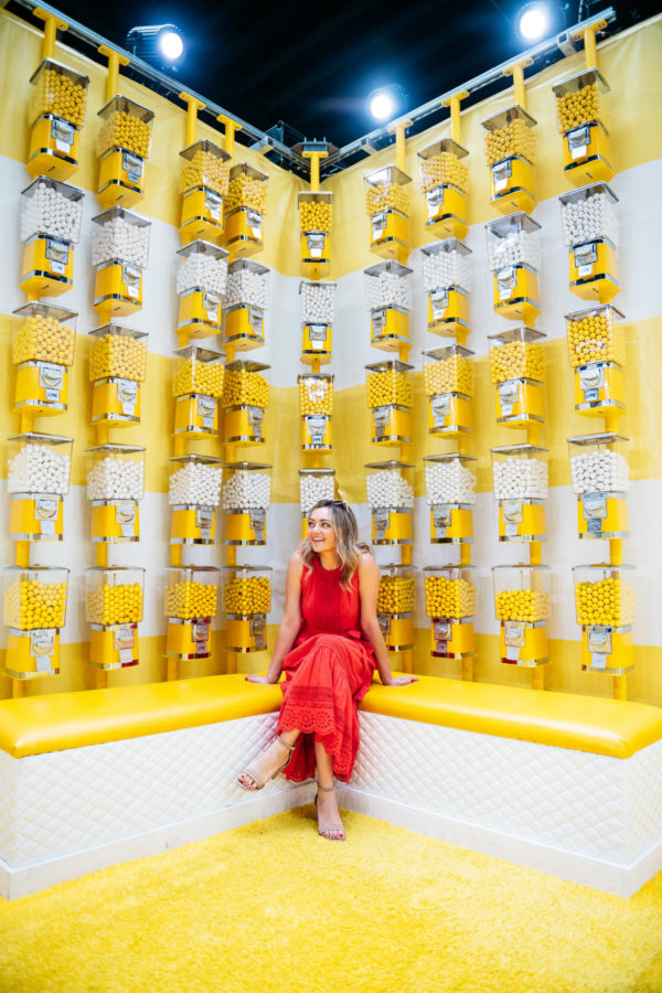 Beauty blogger Jessica Sturdy at Happy Place in Chicago sitting in front of the yellow and white gum ball machines.