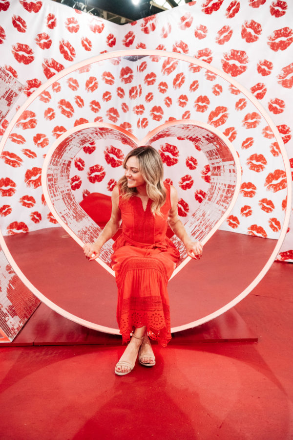 Chicago lifestyle blogger Jessica Sturdy at Happy Place in Chicago in the mirrored love room with red kisses and lips.