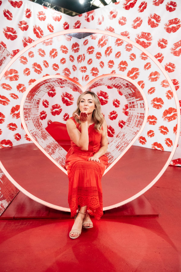 Chicago lifestyle blogger Jessica Sturdy blowing a kiss at Happy Place Chicago in the mirrored heart and red lips room in Chicago