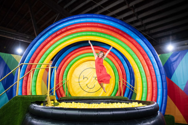 Chicago blogger Jessica Sturdy wearing a coral maxi dress jumping into the rainbow ball pit at Happy Place