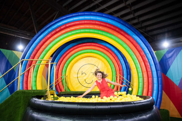 Chicago blogger Bows & Sequins jumping in to a ball pit at Happy Place in a red dress.