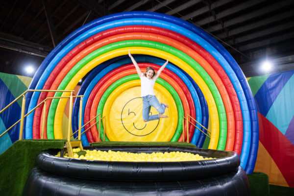 Chicago blogger Jessica Sturdy jumping into a rainbow ball pit at Happy Place