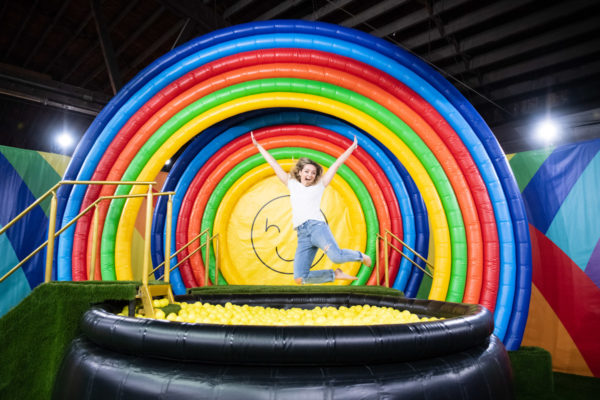 Chicago blogger Bows & Sequins jumping into a rainbow ball pit at Happy Place in Chicago.