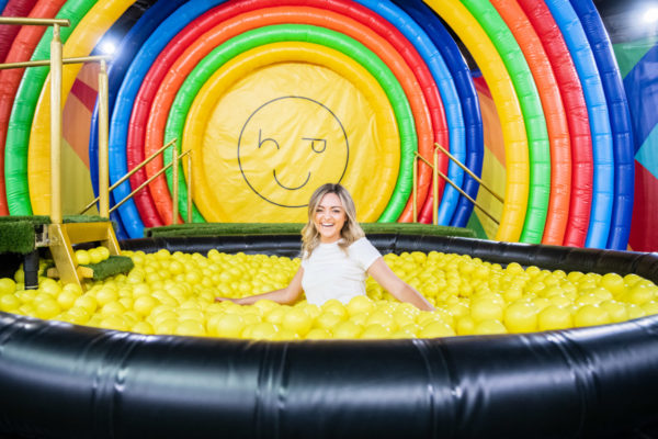 Chicago blogger Bows & Sequins in a rainbow ball pit at Happy Place