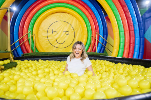 Chicago blogger Bows & Sequins in a yellow ball pit at Happy Place