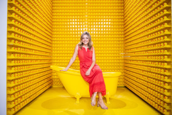 Fashion and lifestyle blogger Jessica Sturdy at Happy Place Chicago posing on the yellow bathtub in the rubber duck room.