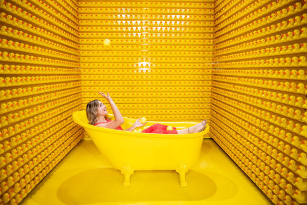 Chicago blogger Jessica Sturdy wearing an orange maxi dress in a yellow bathtub at Happy Place Chicago.