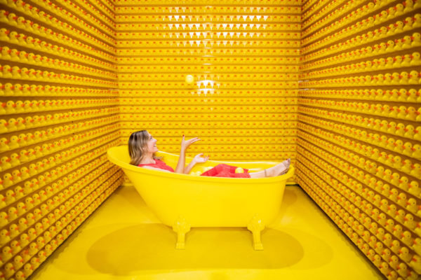 Jessica Sturdy juggling with rubber ducks in a yellow bathtub at Happy Place in Chicago.