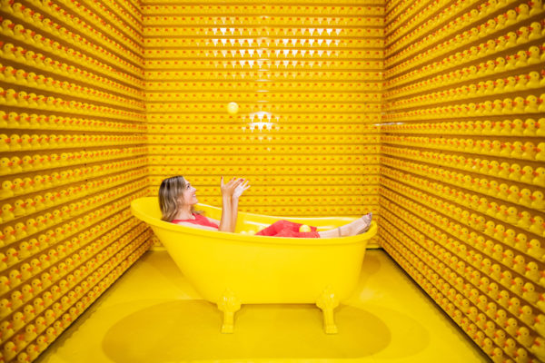 Chicago blogger Jessica Sturdy juggling yellow balls in a bathtub with rubber ducks at Happy Place