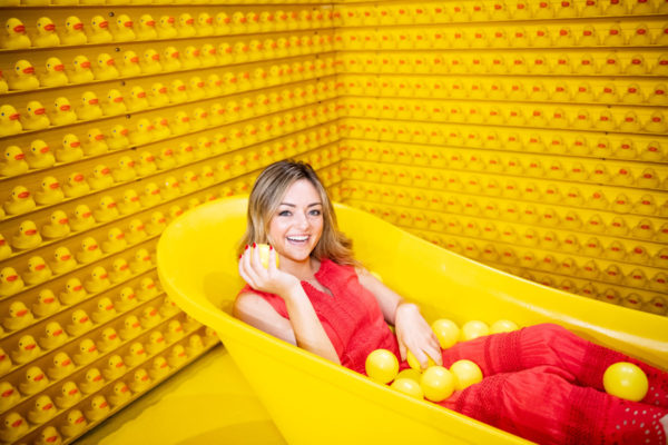 Jessica Sturdy, Chicago-based lifestyle blogger, at Happy Place in the yellow bathtub with rubber ducks.