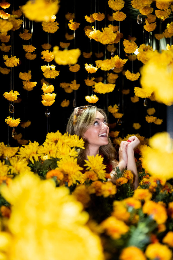 Lifestyle blogger Bows & Sequins at Happy Place Chicago in the room with falling yellow daisies.