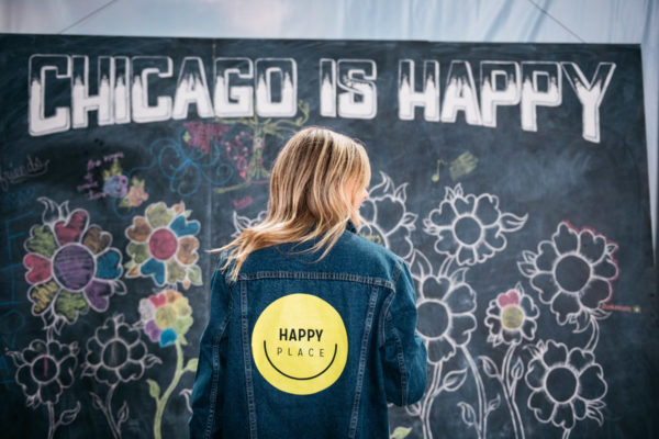 Chicago blogger Jessica Sturdy at Happy Place in Chicago wearing a denim jacket with yellow smiley face.