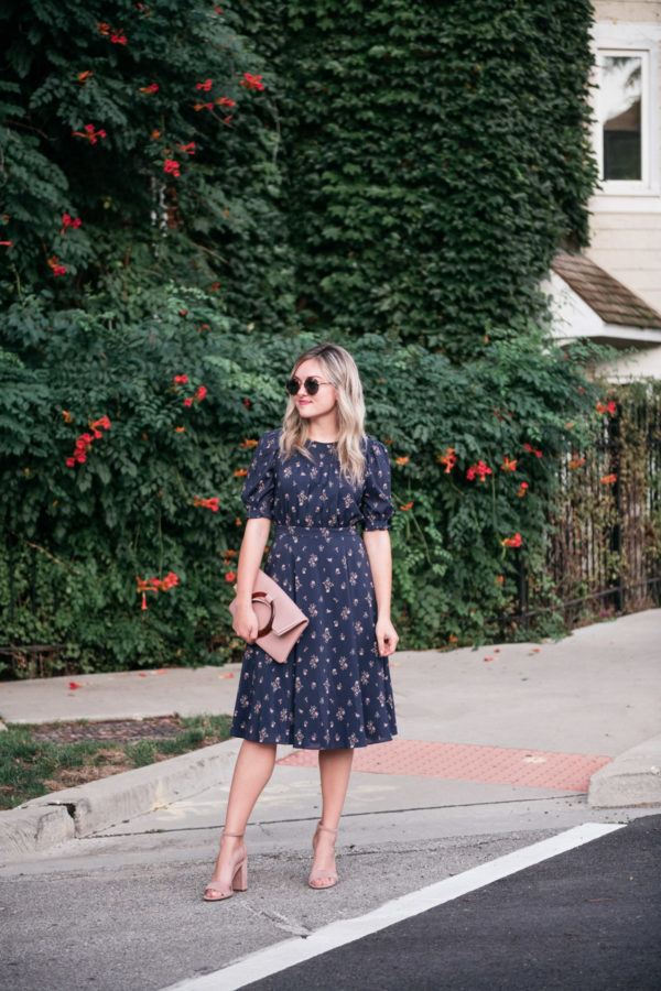 Jessica Sturdy wearing a navy blue floral midi dress with a blush pink clutch to the Create & Cultivate Conference in Chicago