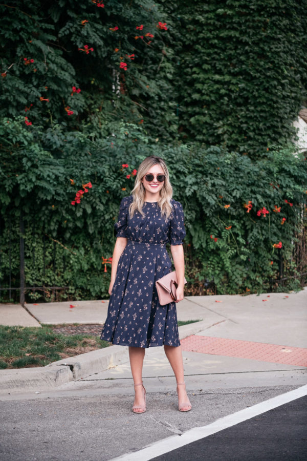 Fashion blogger Jessica Sturdy wearing a floral midi dress with blush pink sandals and a foldover leather clutch.
